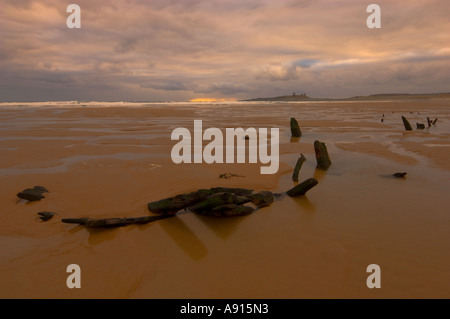 Wooden ship wreck at Embleton Bay with Dunstanburgh castle on the horizon Northumberland UK - Stock Photo