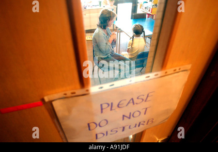 school counsellor talks quietly to a child with Do Not Disturb sign on door - Stock Photo