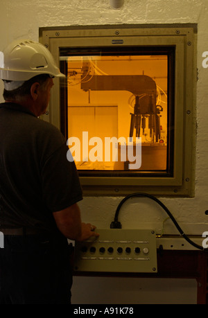 A technician working at a nuclear waste containment chamber - Stock Photo