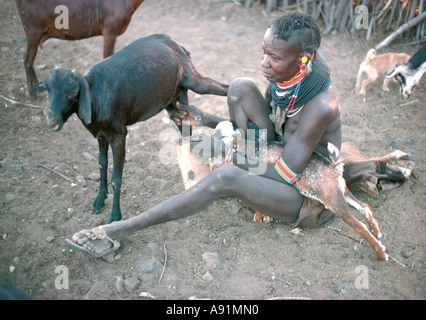 Turkana woman milking a goat into a traditional gourd - Stock Photo