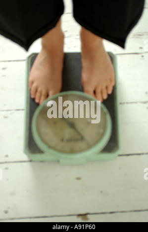 Old Fashioned Weighing scales and feet defocused - Stock Photo