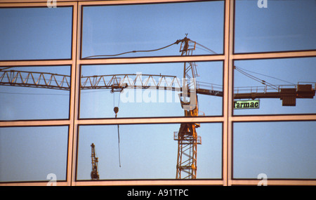 PICTURE CREDIT DOUG BLANE Tarmac crane on building site reflected in the glass building at Central Milton Keynes - Stock Photo