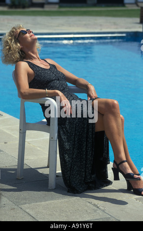 Middle Aged Woman Lounging By Pool With Glasses Of Wine