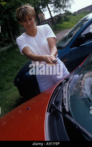 woman trying to open the door of her car with her remote control device - Stock Photo