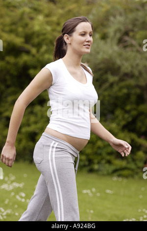 walking happy pregnant woman holding her belly with hands