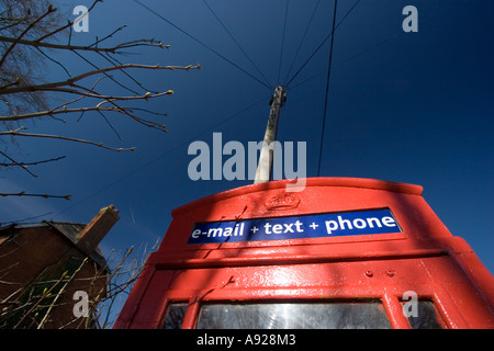 Red telephone box in remote village offering modern SMS text and email services - Stock Photo