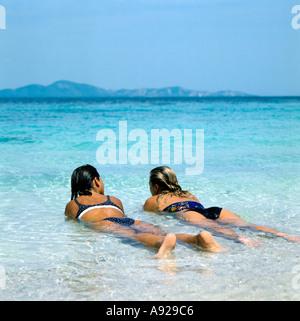 Two girls lying in the shallow water on the uninhabited island of Ko Phai (Bamboo Island) near Pattaya, Thailand - Stock Photo