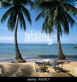 Two deckchairs on quiet corner of the beach in Pattaya, Thailand - Stock Photo