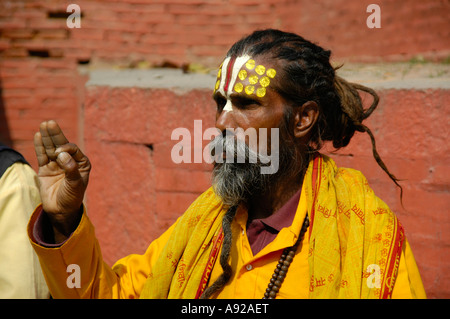 Portrait of a holy man sadhu with a yellow cape and painted forehead Kathmandu Nepal - Stock Photo