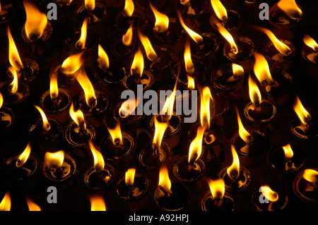 Burning flames of butter lamps in the darkness Kathmandu Nepal - Stock Photo