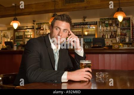 man having a pint in a pub - Stock Photo