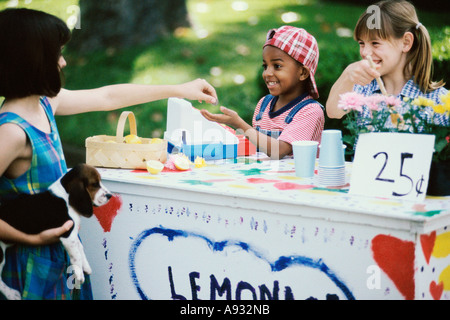 Two girls and a boy standing at a lemonade stand - Stock Photo