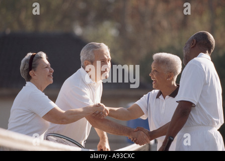 Side profile of two senior couples shaking hands on a tennis court - Stock Photo