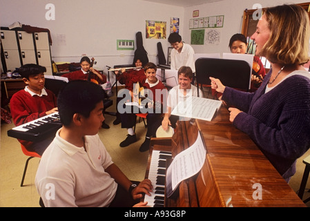 Music class in junior school class room with enthusiastic female teacher conducting a rehearsal - Stock Photo