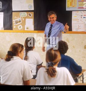 Teacher pointing to teenage pupil in senior school classroom - Stock Photo