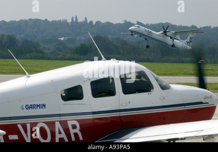 Flybe plane taking off from Southampton Airport with light aircraft waiting on runway. - Stock Photo