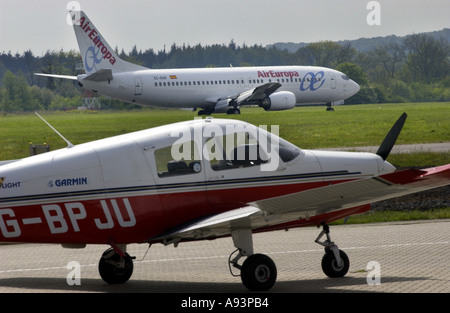 AirEuropa plane landing at Southampton Airport with light aircraft on runway in foreground - Stock Photo