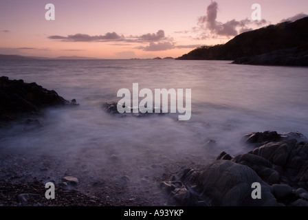 Misty waves crash upon a rocky pebble beach at sunset creating eery mystical imagery of scotland - Stock Photo