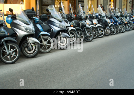 Horizontal close up of a row of many mopeds and scooters parked on the roadside in Florence. - Stock Photo
