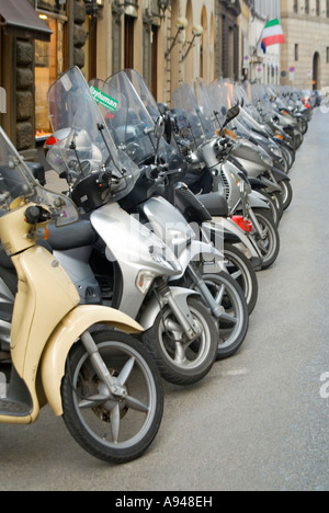 Vertical close up of a row of many mopeds and scooters parked on the roadside in Florence. - Stock Photo