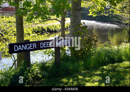 danger deep water warning sign by the river in garvagh forest - Stock Photo