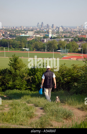 man walking dog on Parliament Hill Hampstead Heath with view over London - Stock Photo