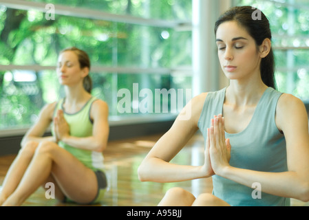 Young women sitting with eyes closed and hands in prayer position during yoga class - Stock Photo