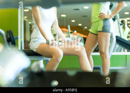 Two women standing in weight room, partial view - Stock Photo