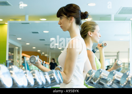 Two women working out with dumbbells - Stock Photo