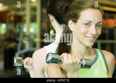 Two women lifting dumbbells, back to back - Stock Photo