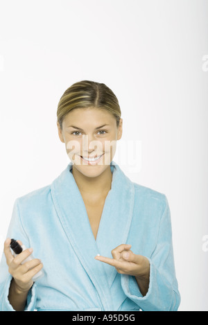 Young woman holding drop of moisturizer on finger, wearing bathrobe, smiling at camera - Stock Photo