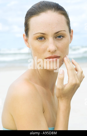 Woman applying sunscreen to face at beach, head and shoulders, portrait - Stock Photo