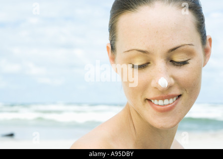 Woman on beach with sunscreen on nose, head and shoulders - Stock Photo