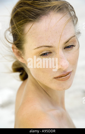 Woman looking over shoulder, hair being tousled by the wind, head and shoulders - Stock Photo