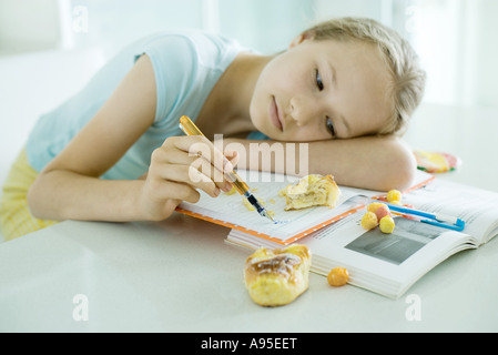 Girl sitting at table doing homework, resting head on arm, doodling, food scattered on books - Stock Photo