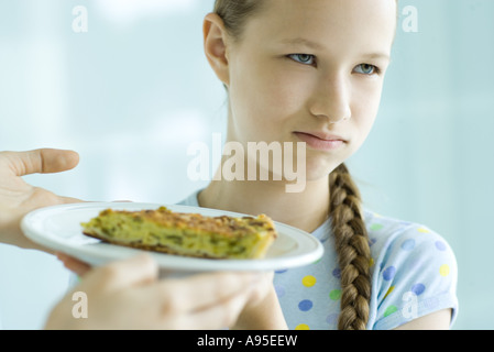 Hands holding up slice of quiche toward girl, girl making face and looking away - Stock Photo