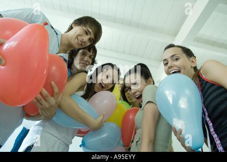 Teenage friends holding balloons - Stock Photo