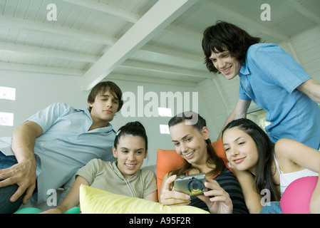 Teenage friends looking at digital camera together - Stock Photo
