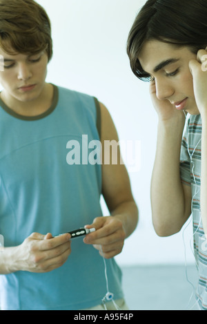 Teenage boys listening to MP3 player - Stock Photo
