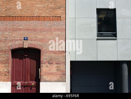 Close-up of two building facades, one in red brick and the other in concrete - Stock Photo