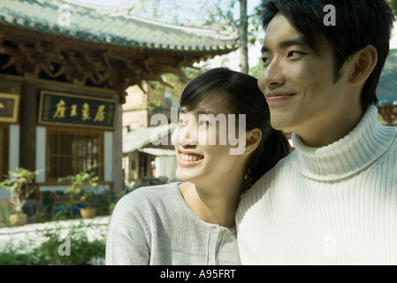 Young couple looking away, smiling, portrait - Stock Photo