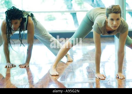 Young adults doing prasarita padottanasana pose in yoga class - Stock Photo