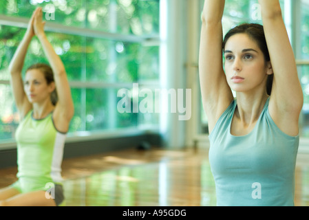 Women kneeling with arms raised overhead - Stock Photo