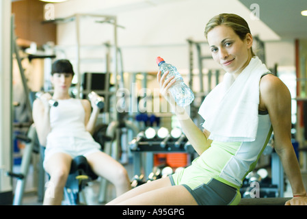 Two women in weight room, focus on woman holding bottle of water - Stock Photo