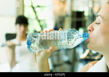 Two women in weight room, focus on woman in foreground drinking bottle of water - Stock Photo