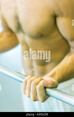 Man lifting barbell, close-up of mid section - Stock Photo