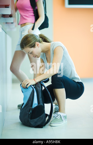 Young woman at health club counter, crouching and looking in backpack - Stock Photo