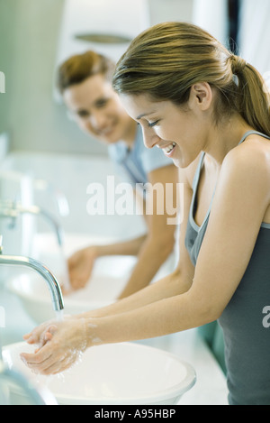 Two women washing hands in public restrooms - Stock Photo