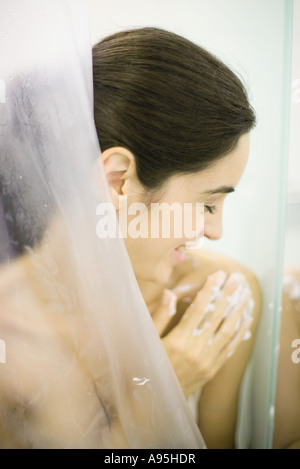 Woman in shower, washing shoulder - Stock Photo