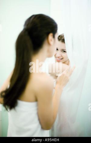 Woman peeking at friend behind shower curtain - Stock Photo